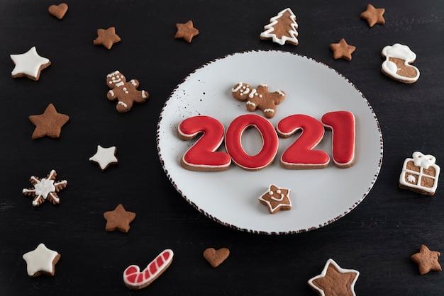 テーブルの上のさまざまなクリスマスクッキー。プレート上の番号2021。クリスマスのベーキング。
