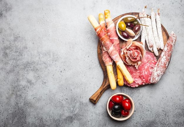 さまざまなハムのカットと前菜、生ハム、ハモン、サラミスライス、ソーセージ、グリッシーニ、オリーブ。素朴な木の板に肉の盛り合わせ、テキスト用のスペース、上面図、クローズアップ