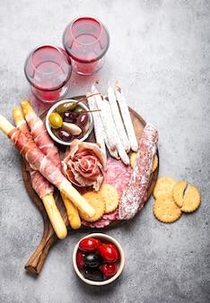 さまざまなハムのカットと前菜、赤ワイン、生ハム、ハモン、サラミスライス、ソーセージ、グリッシーニ、オリーブ。素朴な木の板、灰色の石の背景、上面図、クローズアップの肉の盛り合わせミックス