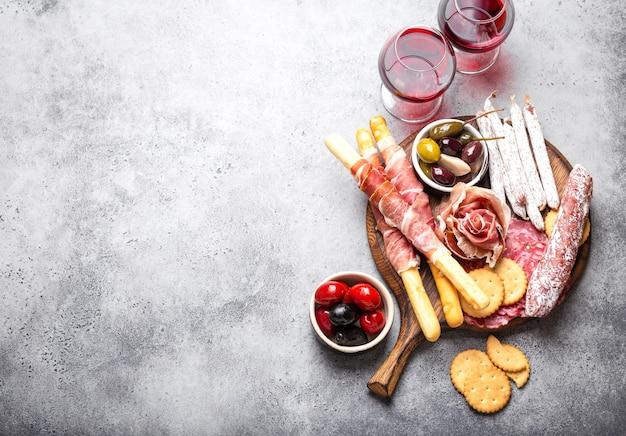 さまざまなハムのカットと前菜、赤ワイン、生ハム、ハモン、サラミスライス、ソーセージ、グリッシーニ、オリーブ。素朴な木の板に肉の盛り合わせ、テキスト用のスペース、上面図、クローズアップ