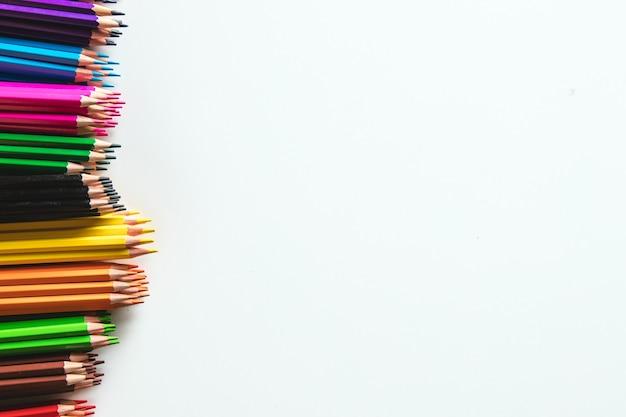 白い壁に分離されたさまざまな色鉛筆