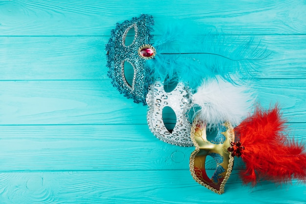 テーブルの上の羽を持つカラフルな仮面舞踏会カーニバルマスクの様々な