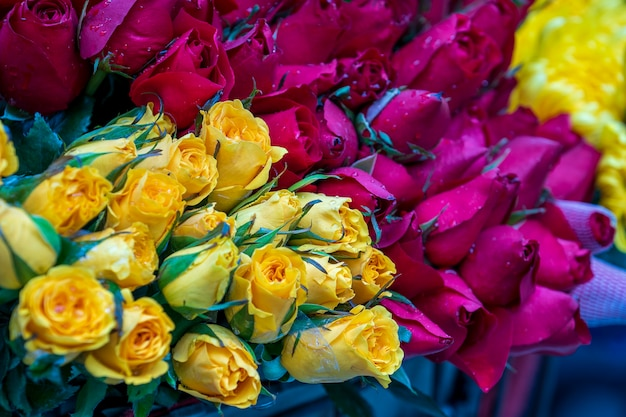 Разнообразие разноцветных розовых цветов, упакованных в пучки, для продажи на уличном рынке