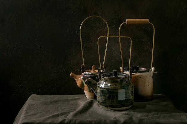 暗い部屋のリネンのテーブルクロスの上に立っているお茶の儀式のためのクラフト手作りセラミックティーポットケトルの様々な。コピースペース