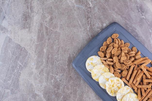 Разнообразие хрустящих крекеров на темной тарелке. фото высокого качества