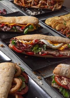 木製のテーブルにさまざまな材料を使ったさまざまなおいしいサンドイッチ。