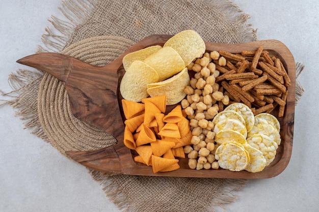 Разнообразие вкусных закусок на деревянной доске.