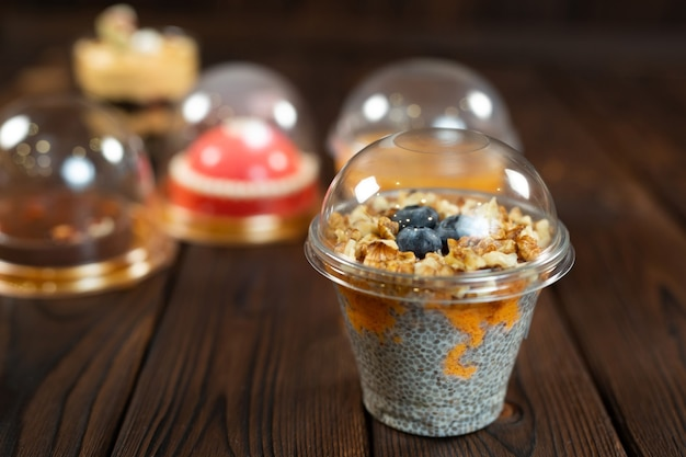 茶色の木製の背景にチアプディングを含む、カップに入ったさまざまなデザート。