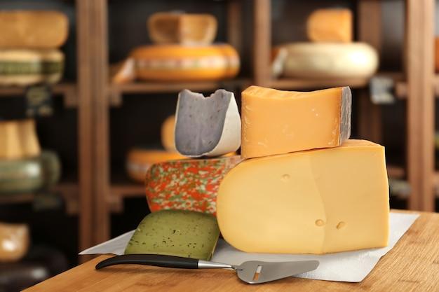 Разнообразие разных сыров на деревянном столе в магазине
