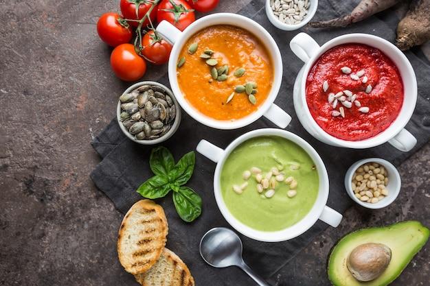 ボウルにさまざまな色とりどりの野菜クリームスープ、上面図。健康的な食事または菜食主義の食糧の概念。