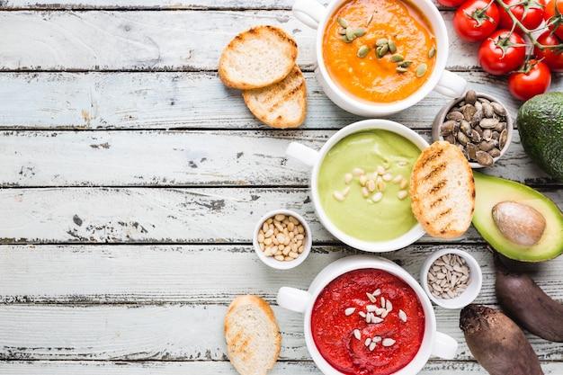 Разнообразие различных красочных овощных крем-супов в мисках, вид сверху. концепция здорового питания или вегетарианской пищи.