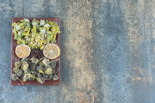 Разнообразие сушеных цветов на коричневой тарелке.