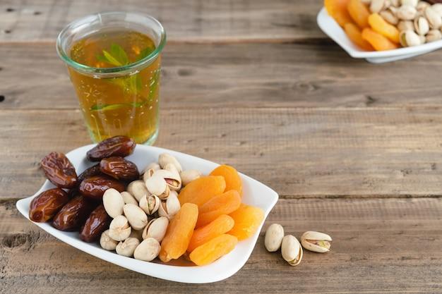 나무 배경에 민트 차 한 잔을 곁들인 다양한 말린 과일. 공간을 복사합니다.