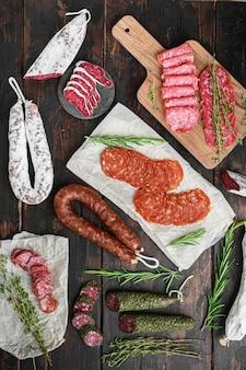 Разнообразие сыровяленых чоризо, фуэт и других колбас, нарезанных ломтиками с зеленью на темном деревянном фоне.