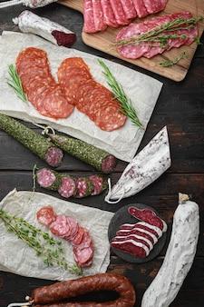 Разнообразие сыровяленых чоризо, фуэ и других колбас, нарезанных ломтиками с зеленью на темной деревянной поверхности, вид сверху.