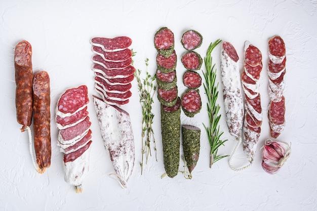Разновидности сыровяленых колбас с фуэтом и чоризосалами, целые и нарезанные на белой поверхности, плоской выкладки.