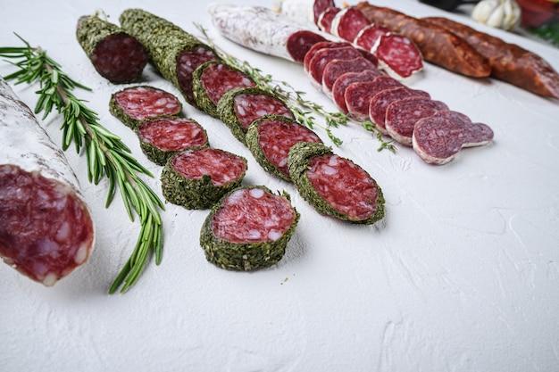 Разнообразие сыровяленых колбас фуэт и чоризосалами, целых и нарезанных на белом текстурированном фоне с пространством для текста.