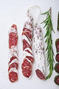 Разнообразие сыровяленых колбас фуэ и чоризосалами, целых и нарезанных на белом текстурированном фоне.
