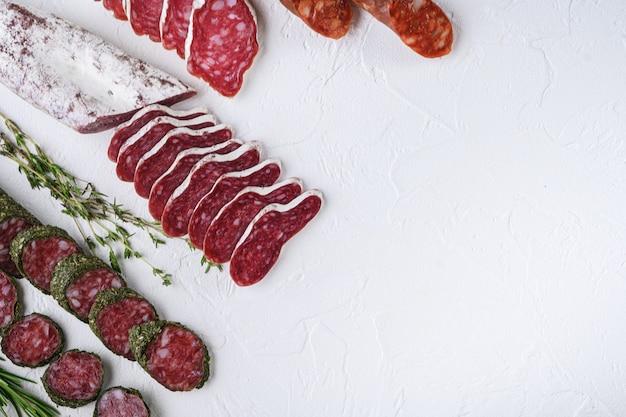 Разнообразие сыровяленых колбас фуэт и чоризосалами, целых и нарезанных на белой текстурированной поверхности, вид сверху с местом для текста.