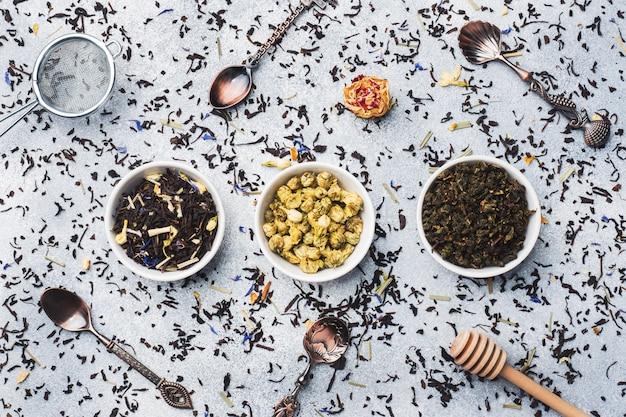 乾燥茶葉と灰色の背景上にボウルの花の様々な。