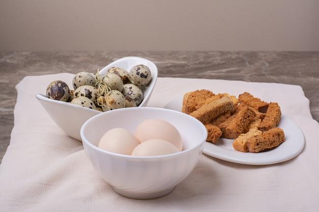 Разнообразие яиц в чашке на серой поверхности