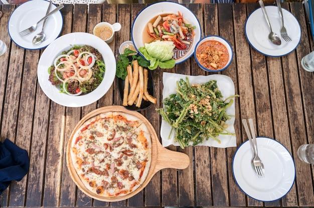 Разнообразие блюд с пиццей, мясным сыром, хрустящими овощами, острым салатом и посудой на деревянном столе в ресторане