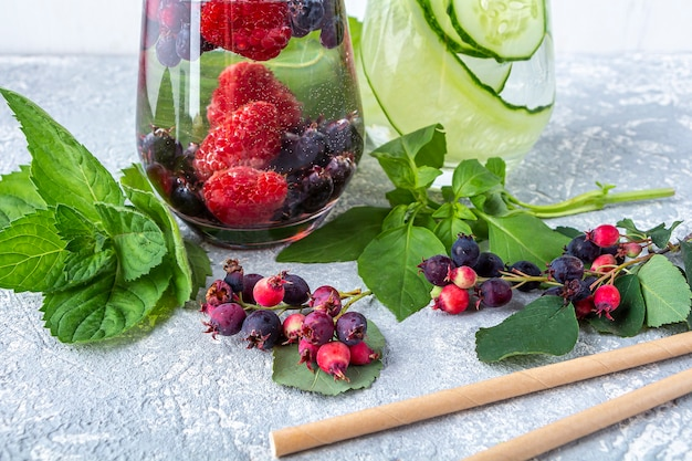 Разнообразие освежающих прохладительных напитков детокс с ягодами и огурцом.