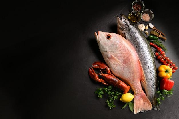 Разнообразие свежей рыбы и морепродуктов на черной каменной поверхности