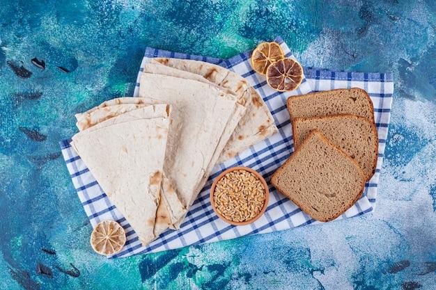 青い表面に大麦のボウルが付いている新鮮な香りのよいパンの様々な。