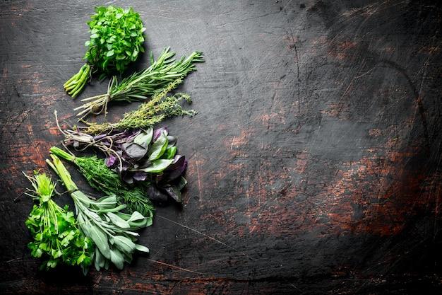 Разнообразие свежих зеленых трав на темном деревенском столе.