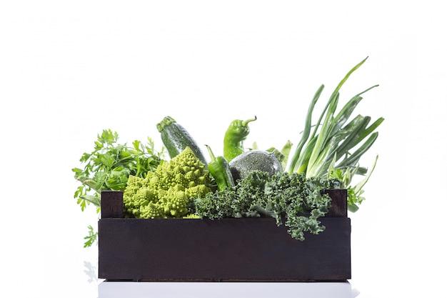 木製の箱、白い背景で隔離の新鮮な緑の野菜各種。