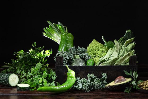 暗い背景の木の木製の箱で新鮮な緑の野菜各種。