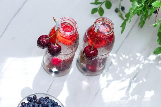 Разнообразие фруктов с детокс-водой в стеклянных бутылочках. освежающие летние напитки. концепция здорового питания.