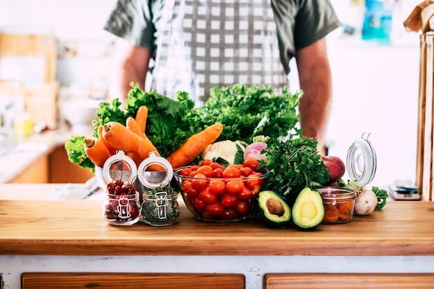 家庭やキッチンレストランでのさまざまな果物や野菜、食事とベジタリアンまたはビーガンフードの栄養の表面的な概念で認識できないシェフがいる健康的なライフスタイル自然な季節