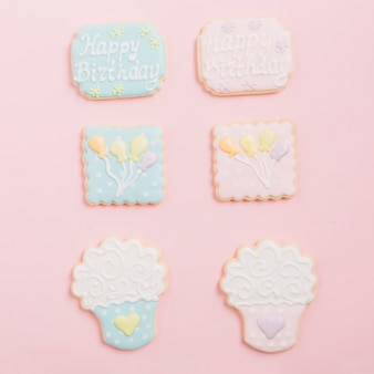 Variety of gingerbread icing cookies arranged on pink background