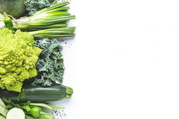 コピースペースと白い背景の上の緑の野菜各種。上面図。