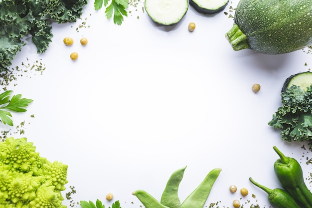 Разнообразие зеленых овощей на белом фоне с копией пространства. вид сверху.
