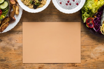 Variety of healthy foods in bowl with blank brown paper on wooden table
