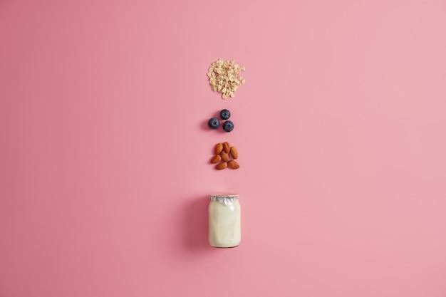 健康的な朝食のためのさまざまな健康的な食材。ヨーグルト、オートミールシリアル、ブルーベリー、アーモンドナッツをピンクの背景に混ぜます。おいしい栄養のお粥を作るためのおいしい製品。食べるコンセプト