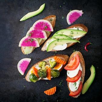 Разнообразие здоровых бутербродов на темной поверхности в деревенском стиле. вид сверху