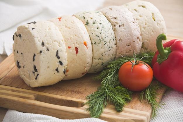 Разнообразие домашних сыров и помидоров перца и зелени на деревянной доске