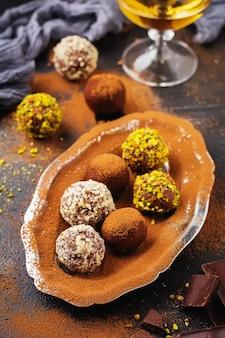 Разнообразие домашних трюфелей из темного шоколада с какао-порошком, фисташками, миндалем темно-коричневой текстуры