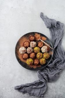 Разнообразие домашних трюфелей из темного шоколада с какао-порошком, фисташками, миндалем светло-серой текстуры