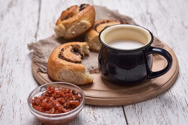 Разнообразие домашнее слоеное тесто булочки с корицей, подается с чашкой молока, вареньем, маслом, как завтрак на белой доске деревянный стол. плоская планировка, пространство