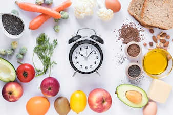 Variety of ingredients with alarm clock arranged against isolated on white background