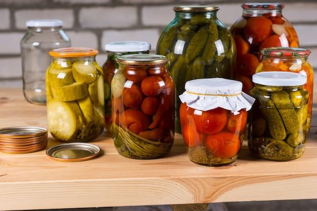木製のテーブルに漬けた野菜のさまざまな瓶、ファーマーズマーケットで販売するための保存野菜の選択