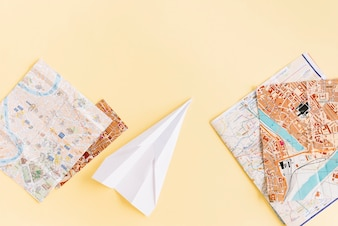 Variety of maps with white paper airplane on beige background