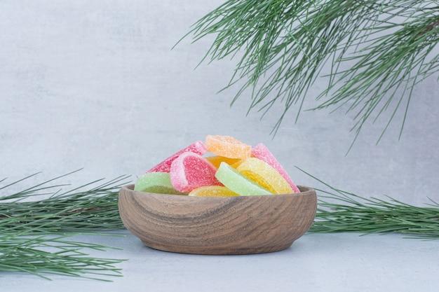 Разнообразие мармеладных конфет в деревянной миске с веткой.