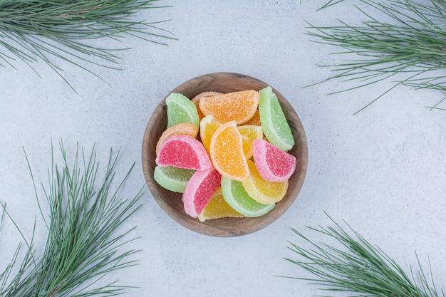 Разнообразие мармеладных конфет в деревянной миске.