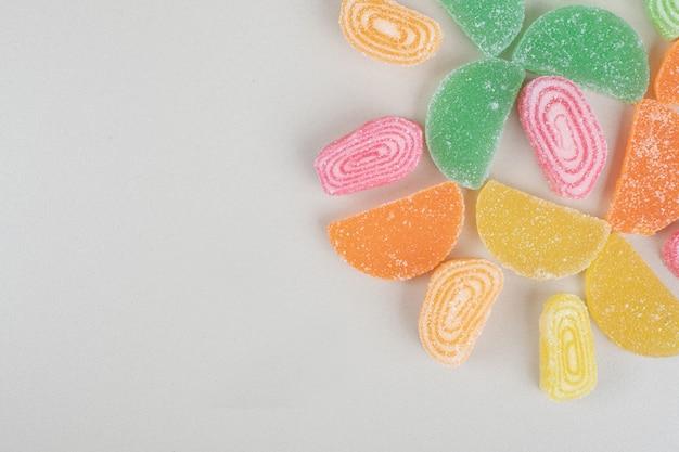 Разнообразие мармеладных конфет на бежевой поверхности